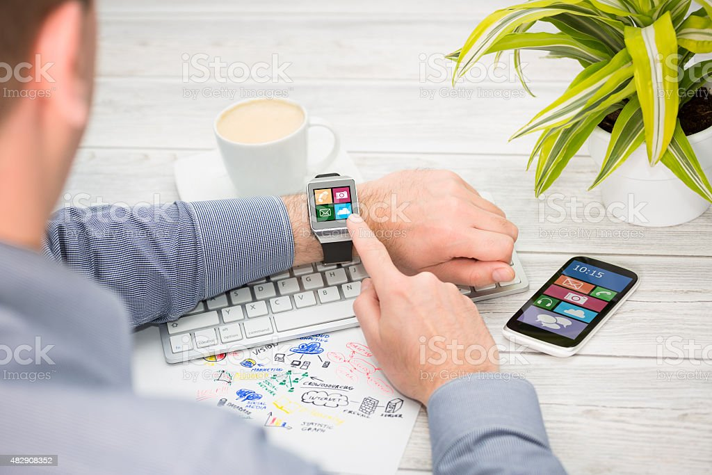 Businessman uses smart watch and phone. stock photo