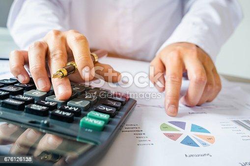 istock Businessman using a calculator to calculate 676126138