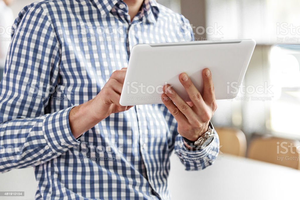 Businessman using a digital tablet in the office Businessman wearing checkered shirt using a digital tablet in an office. Close up of hands, unrecognizable person. 2015 Stock Photo