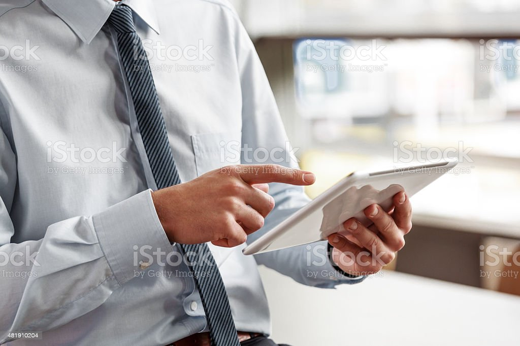 Businessman using a digital tablet in the office Businessman wearing shirt and tie using a digital tablet in an office. Close up of hands, unrecognizable person. 2015 Stock Photo