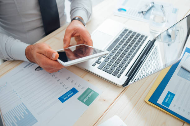 Businessman using a digital tablet Professional businessman working at desk and using a touch screen tablet, technology and communication concept financial report stock pictures, royalty-free photos & images