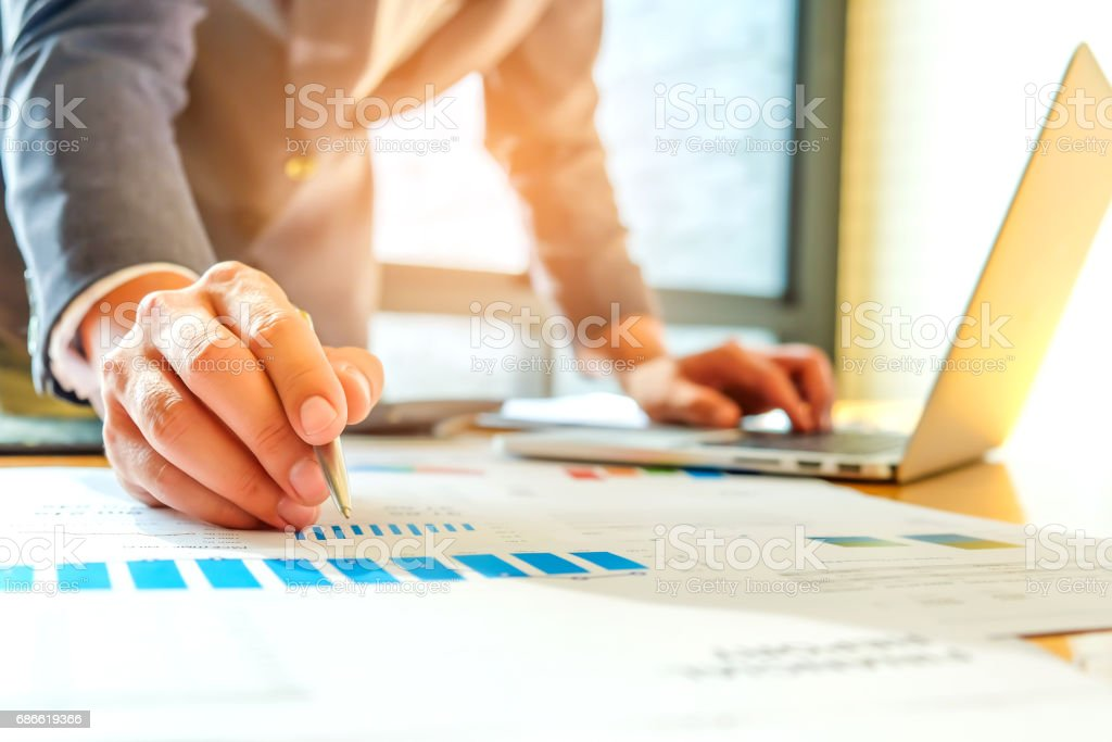 Businessman using a laptop and pen to analyze data. royalty-free stock photo