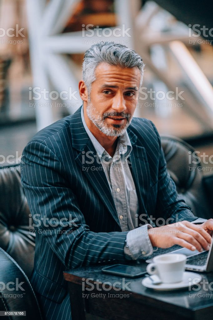 Businessman using a laptop at an internet cafe stock photo