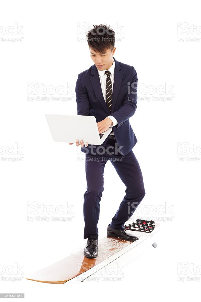 businessman using a laptop on a  surfboard stock photo