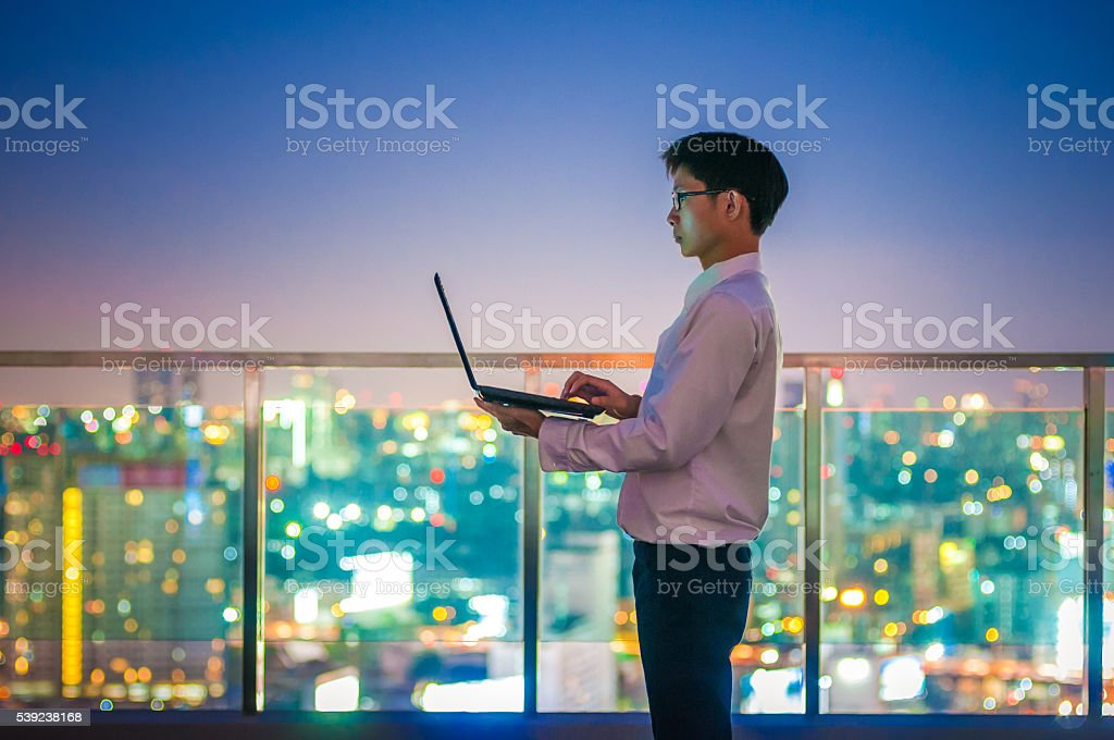 Businessman using a laptop on the rooftop of a skyscraper royalty-free stock photo