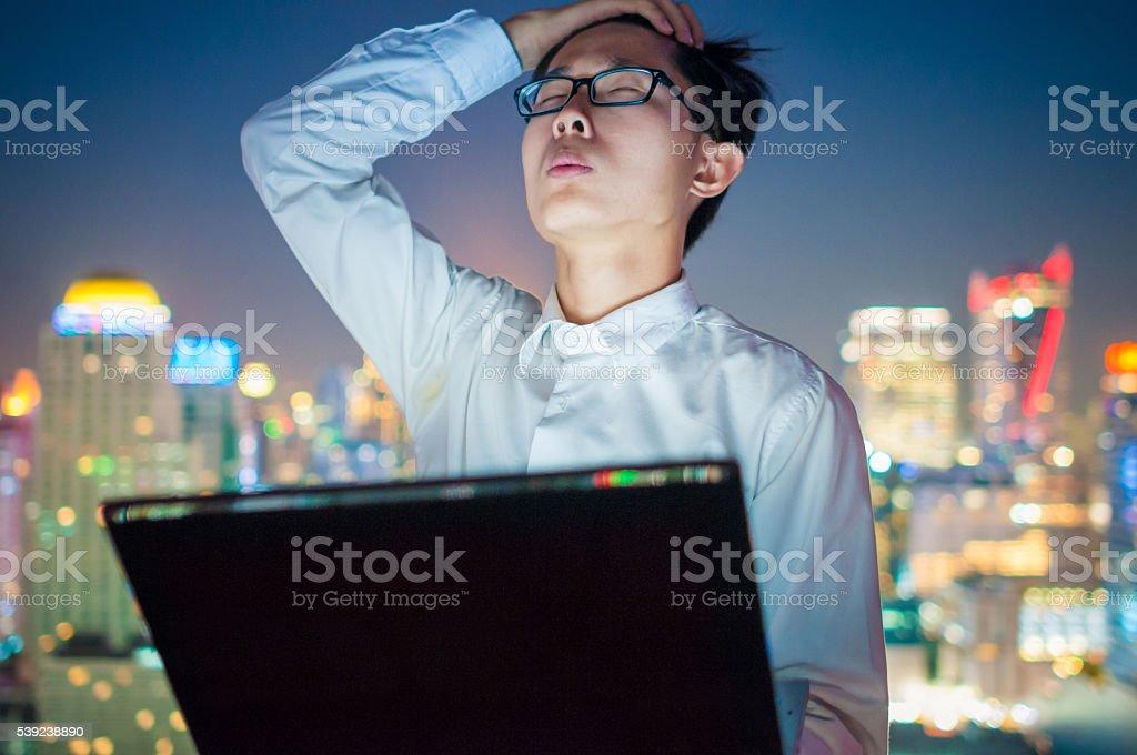 Hombre de negocios usando una computadora portátil en el último piso de un rascacielos foto de stock libre de derechos