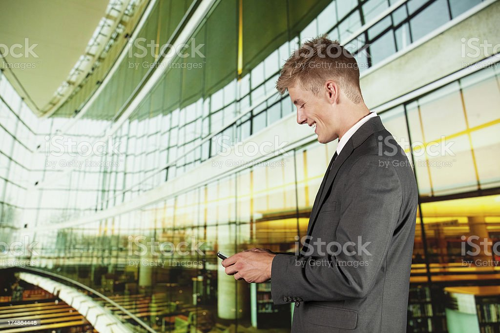 Businessman using a mobile phone and smiling royalty-free stock photo