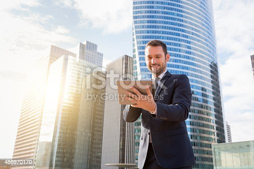 istock Businessman using a phone and digital tablet 486970170