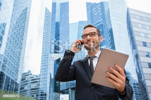 istock Businessman using a phone and digital tablet 489090570