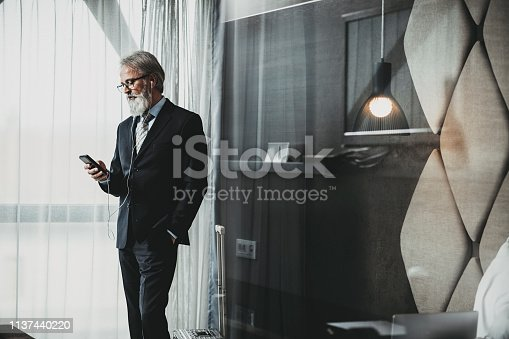 istock Businessman using a phone in hotel room 1137440220
