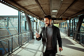 Close up of a young businessman using his phone at a railroad station
