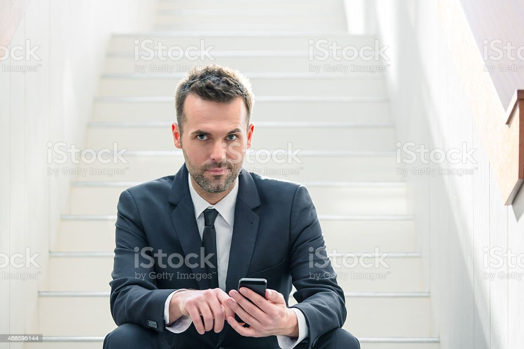 Businessman using a smart phone Portrait of confident businessman wearing dark suit sitting on white stairs in an office and using a smart phone, looking at camera. 2015 Stock Photo