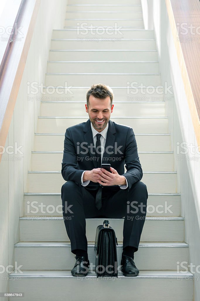 Businessman using a smart phone Full lenght portrait smiling businessman sitting on stairs in an office and using a smart phone. 2015 Stock Photo