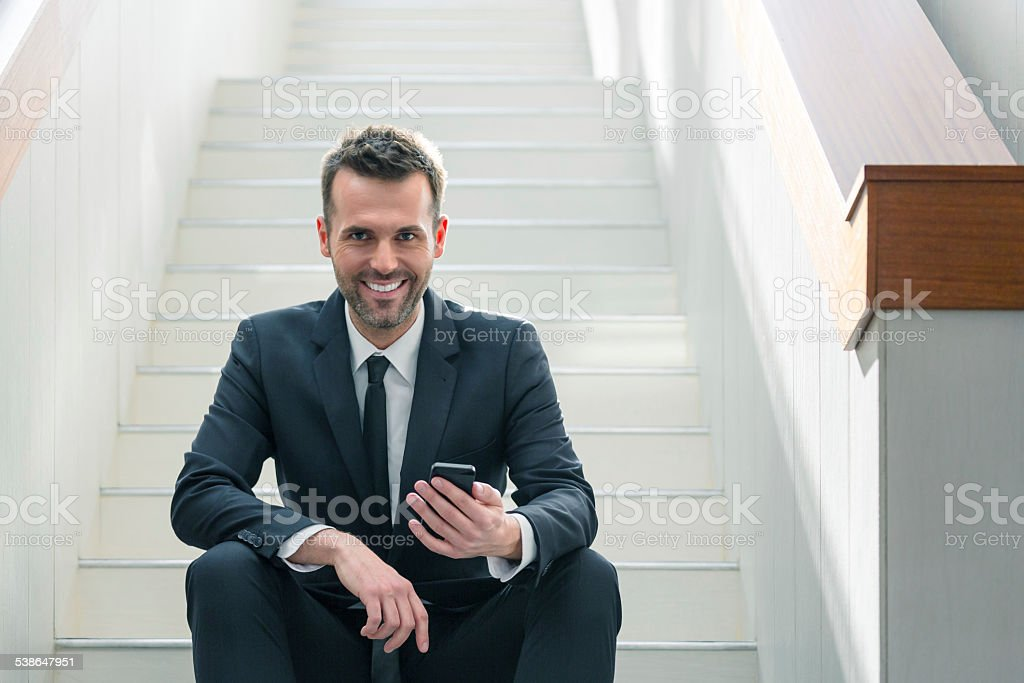 Businessman using a smart phone Portrait smiling businessman sitting on stairs in an office and using a smart phone, smiling at camera. 2015 Stock Photo
