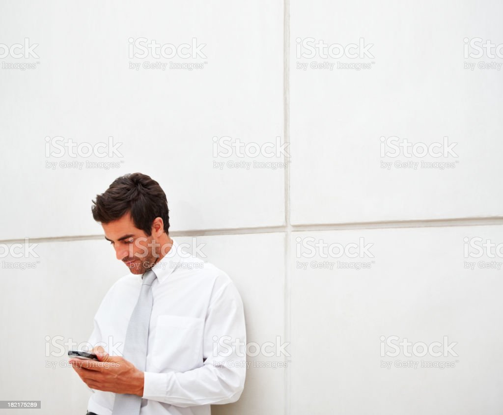 Businessman using a smartphone while leaving on a white wall royalty-free stock photo