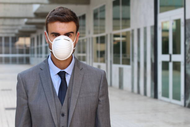 Businessman using an anti-pollution mask Businessman using an anti-pollution mask. antipollution stock pictures, royalty-free photos & images