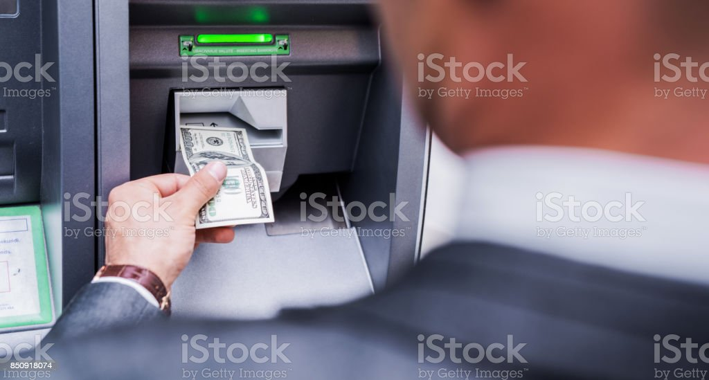 Businessman using an ATM machine stock photo