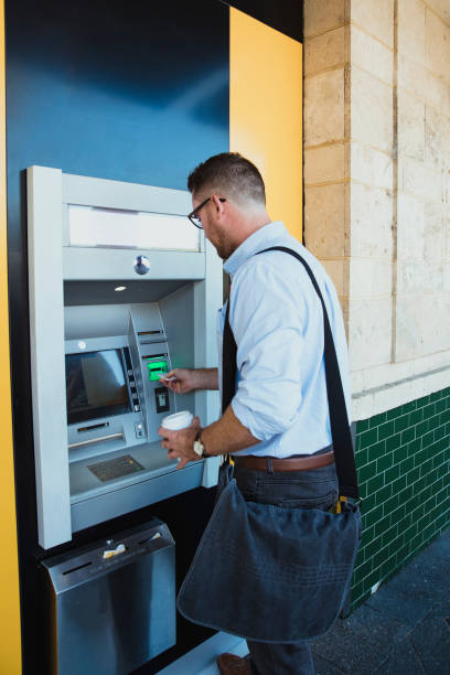 Businessman Using ATM Machine A rear-view shot of a caucasian businessman using an ATM machine in Perth Australia, he is inserting his credit card to withdraw money. banks and atms stock pictures, royalty-free photos & images