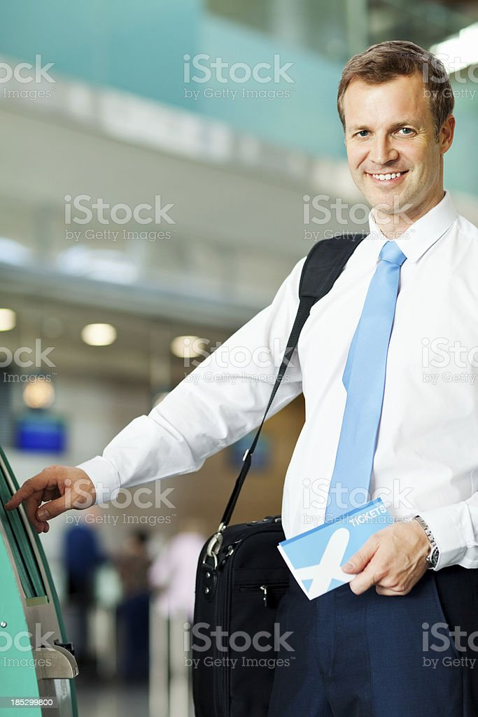 Businessman checks in with a self-service check-in machine at the...