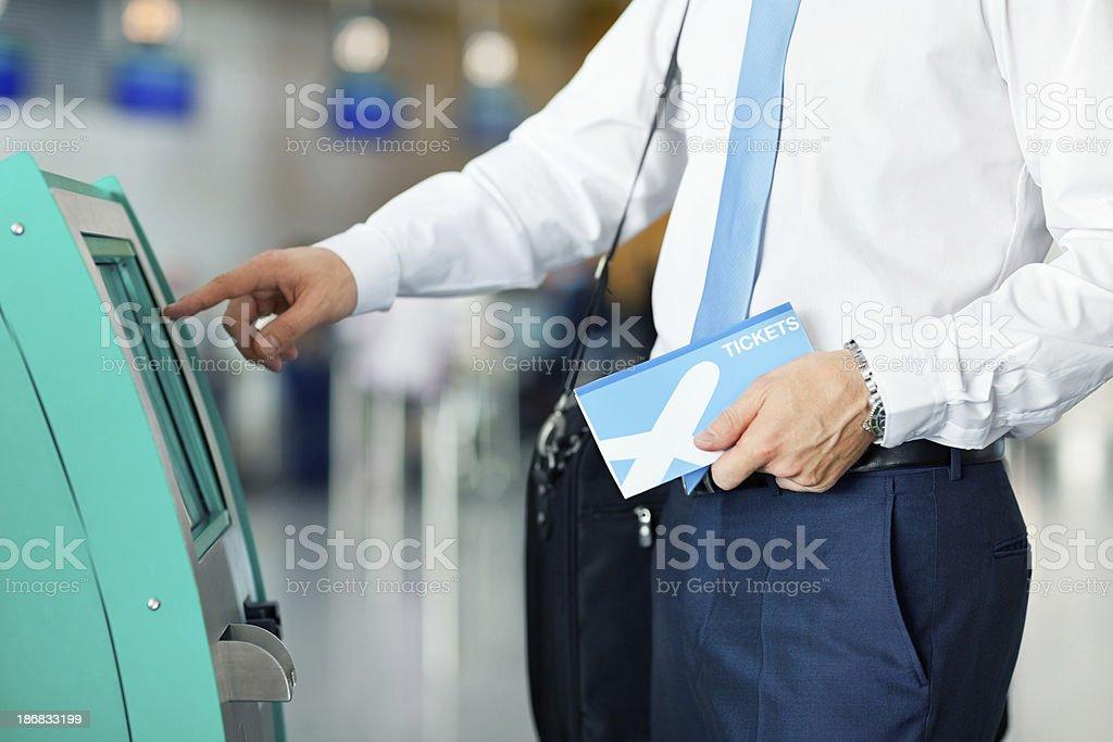 Geschäftsmann mit automatischer Check-In-Automaten am Flughafen Lizenzfreies stock-foto