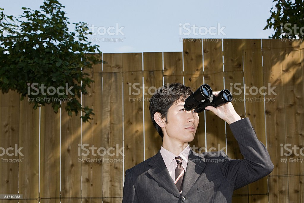 A businessman using binoculars royalty-free stock photo