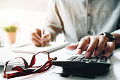 istock Businessman using calculator during note some data on notepad for calculate financial - Bookkeeper Accounting Concept 1053290578
