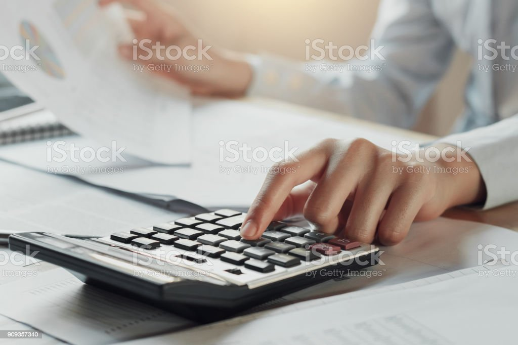 businessman using calculator for calculate budget on table in office. concept finance and accounting stock photo