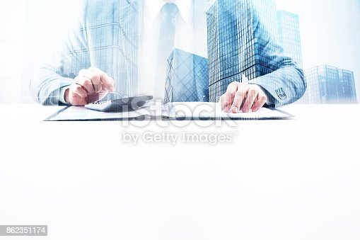 Businessman sitting by the desk using calculator with double exposure cityscape.