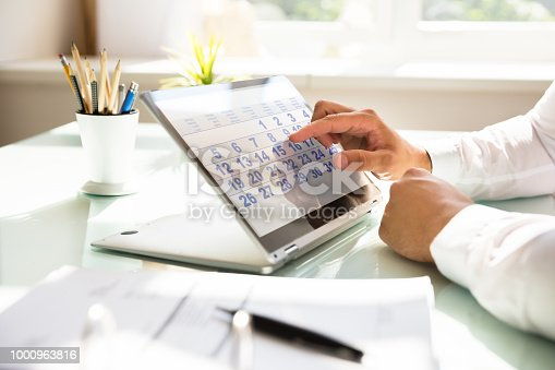 Close-up of a businessman's hand using calendar on laptop over desk