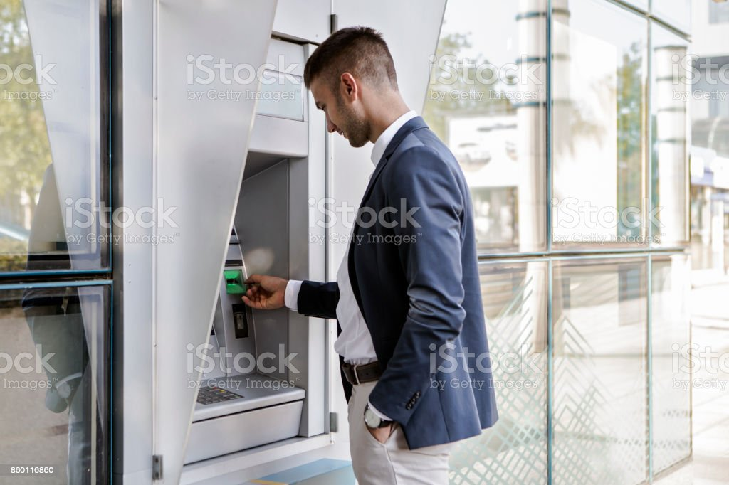 Businessman using card at an ATM stock photo