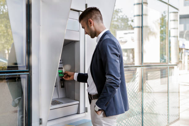 businessman using card at an atm - banks and atms stock pictures, royalty-free photos & images