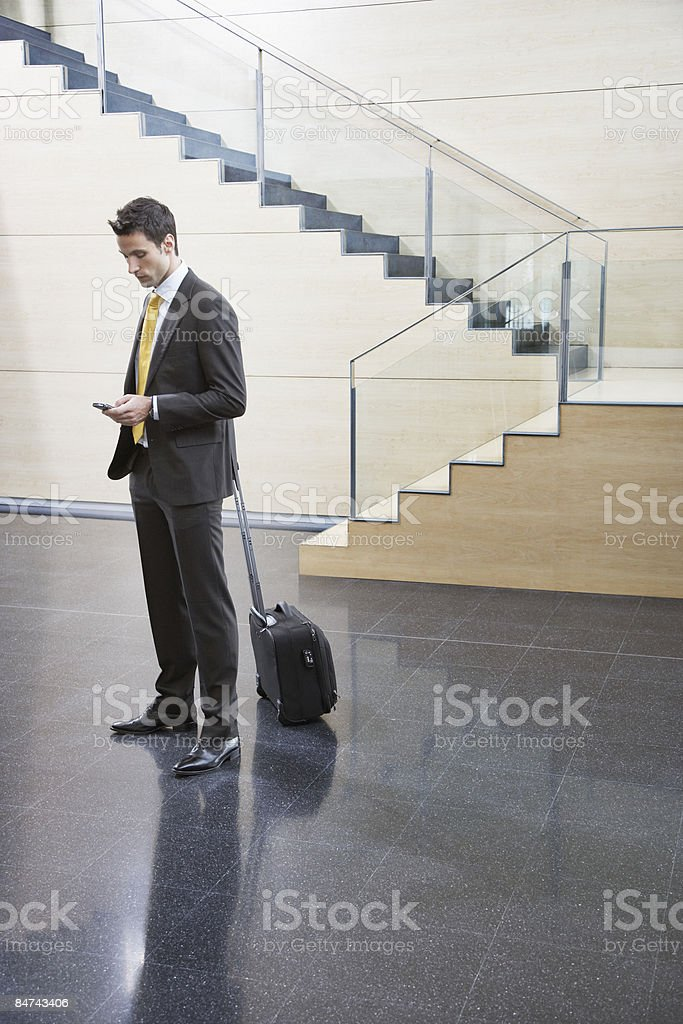 Businessman using cell phone in office lobby royalty-free stock photo