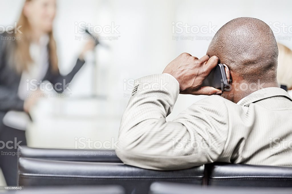 Businessman using cell phone in seminar stock photo