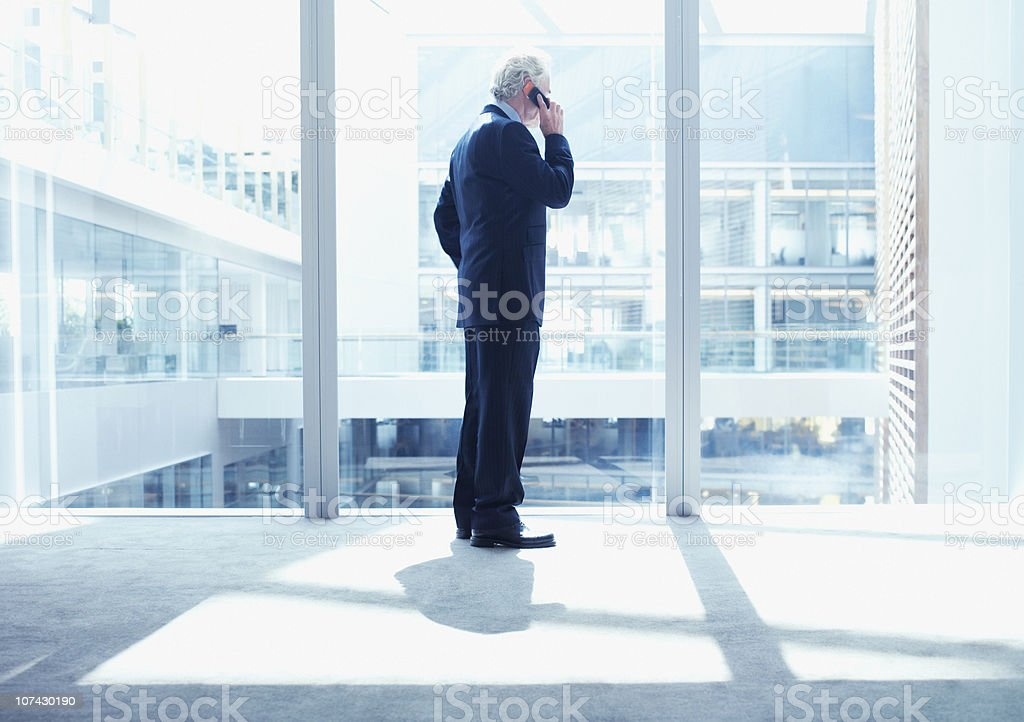 Businessman using cell phone near glass wall in office royalty-free stock photo