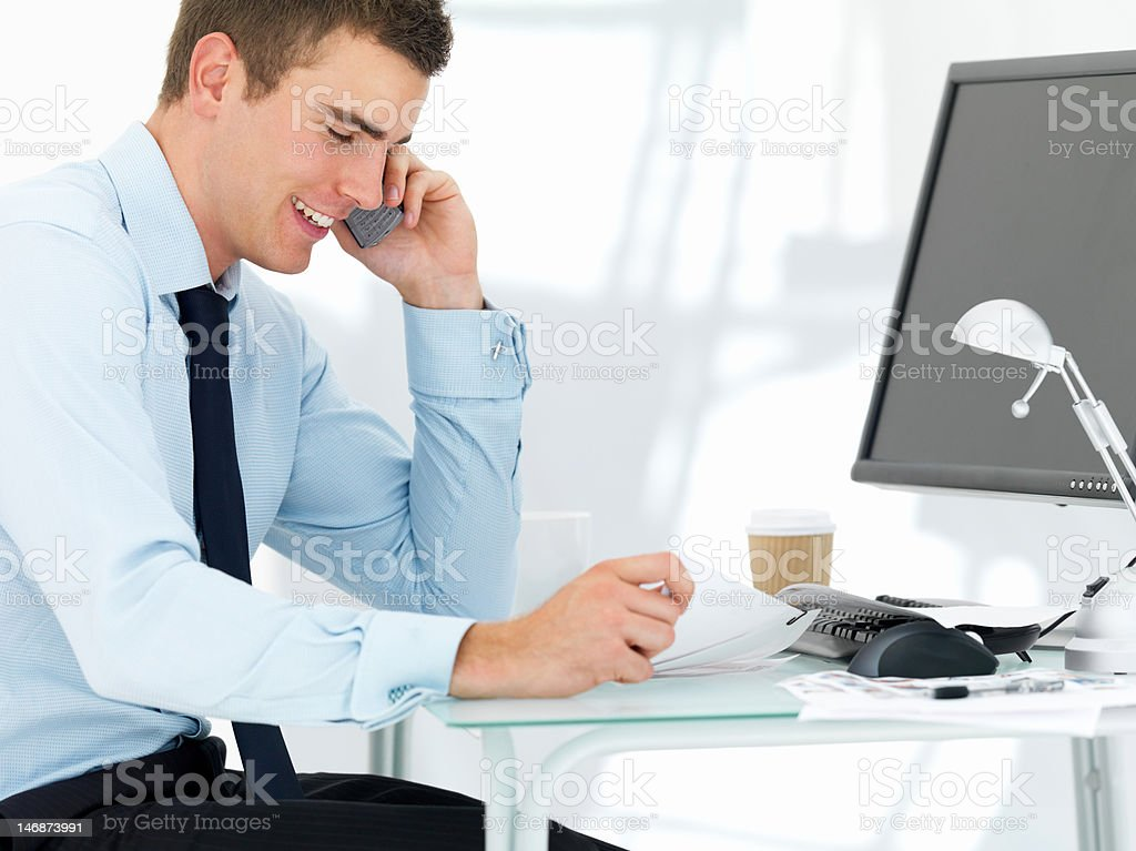 Businessman using cellphone at office desk royalty-free stock photo