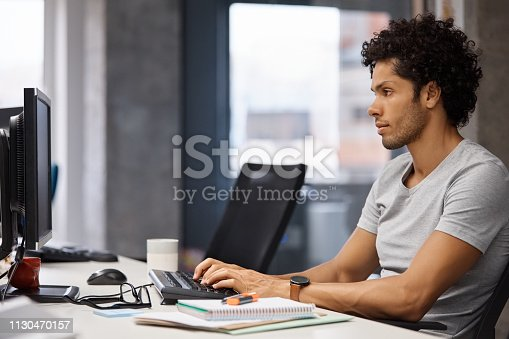 Confident businessman using computer at desk. Male executive is working in creative office. He is wearing smart casuals.