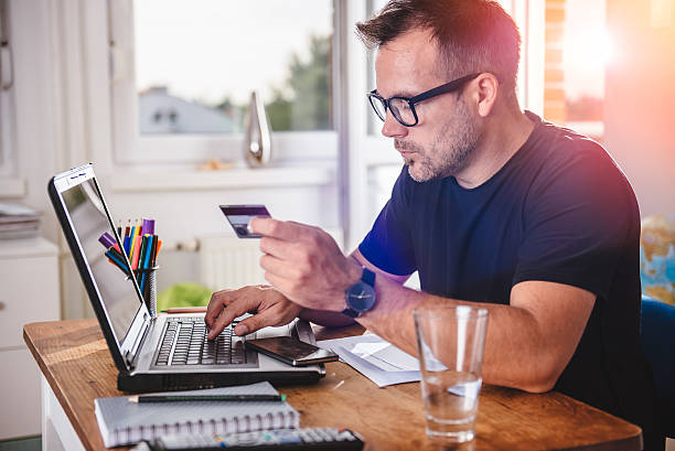 businessman using credit card and laptop - brille bestellen stock-fotos und bilder