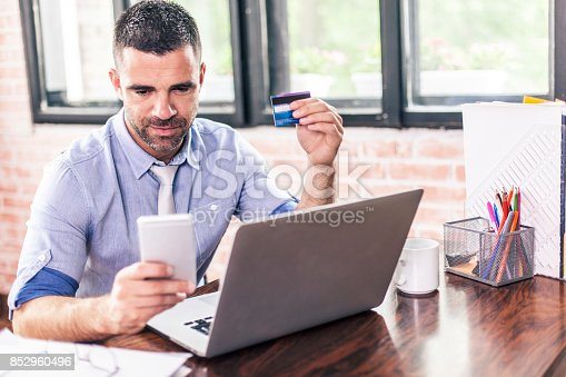 913346608 istock photo Businessman using credit card and smart phone for contactless payment 852960496