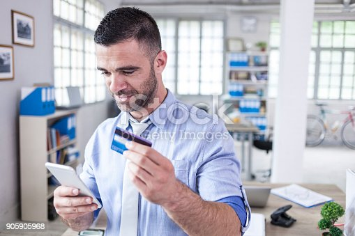 913346608 istock photo Businessman using credit card and smart phone for contactless payment 905905968