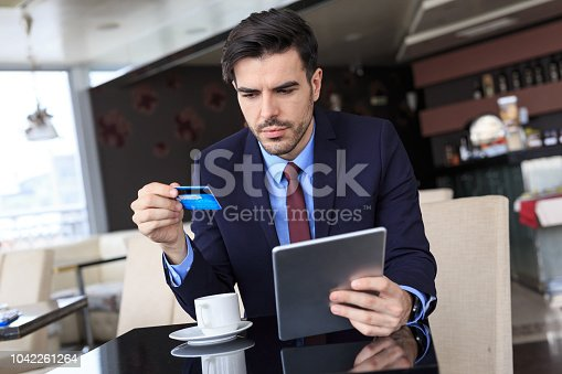 502723248 istock photo Businessman using credit card and tablet in restaurant 1042261264