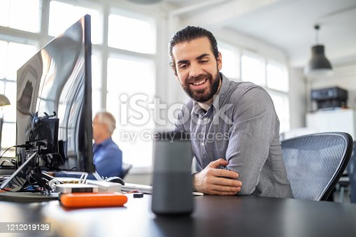 Businessman sitting at his desk talking to smart speaker. Male professional asking digital assistant a question at office.