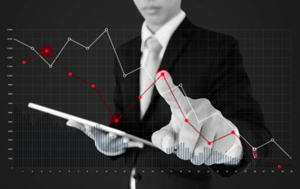 Businessman using digital tablet and pointing finger on falling graph diagram. Business finance and economy crisis stock photo