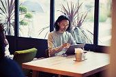 カフェでデジタルタブレットを使うビジネスマン
