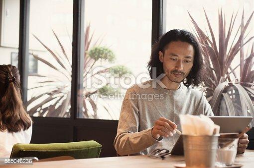 istock Businessman using digital tablet at cafe 585046236