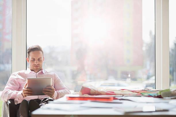 Homem de negócios com tabuleta digital na mesa de conferência no escritório criativo - foto de acervo
