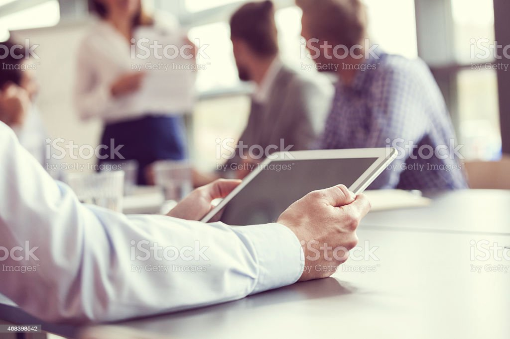 Businessman using digital tablet, close up of hands Close up of businessman's hands holding a digital tablet. In the background blured business team having meeting in a board room in an office, sitting at the conference table and discussing.  2015 Stock Photo