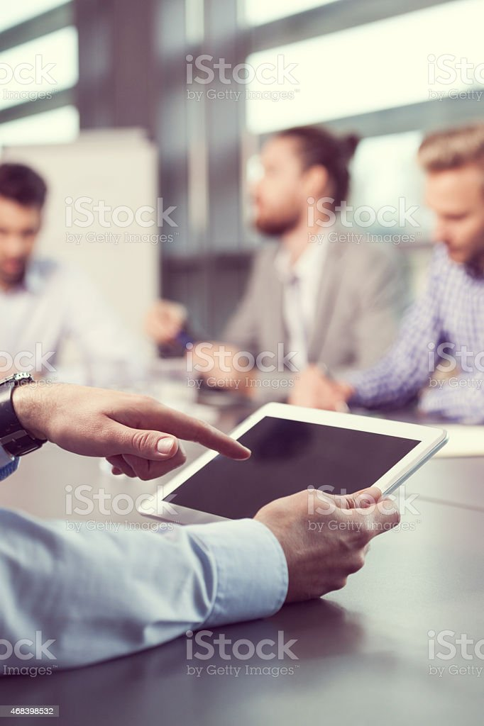 Businessman using digital tablet, close up of touchscreen Close up of businessman's hands holding digital tablet. In the background blured business team having meeting in a board room in an office, sitting at the conference table and discussing.  2015 Stock Photo
