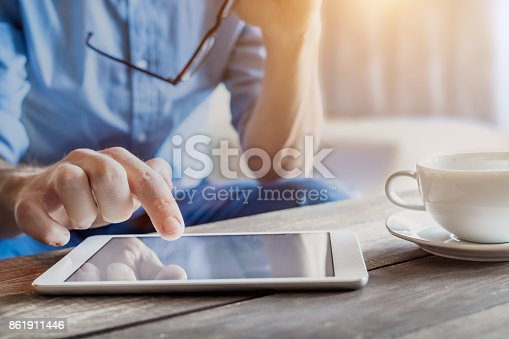 istock Businessman using digital tablet computer on wooden table, coffee, screen 861911446
