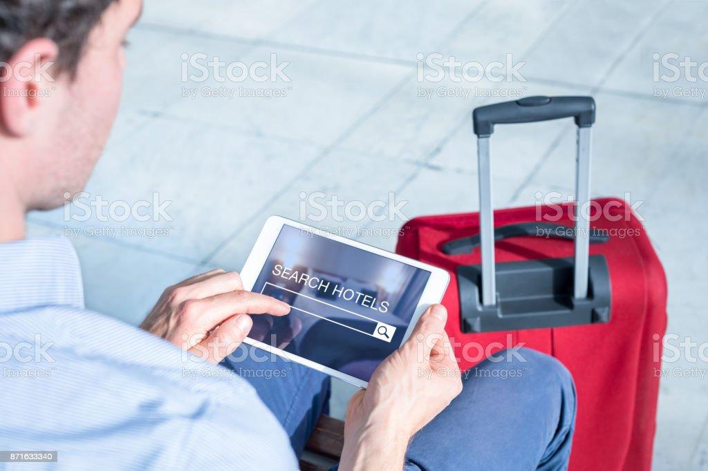 Homme d'affaires en utilisant une tablette numérique pour Rechercher l'hôtel à réserver en ligne - Photo