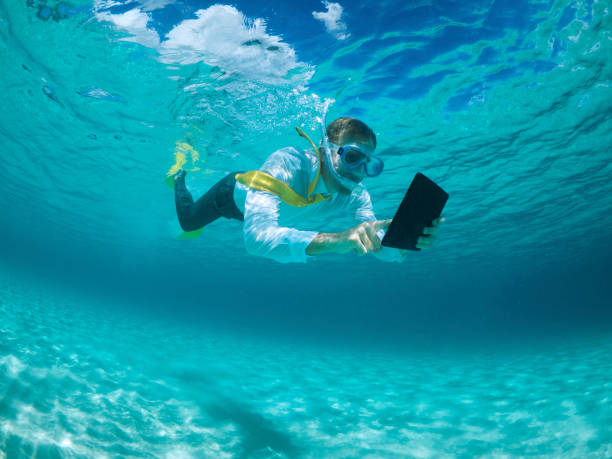 Businessman Using Digital Tablet Computer Underwater Snorkeling stock photo